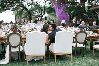 bride-and-groom-in-armchairs-at-head-table-outdoor-reception-hawaii-kiss-newlyweds