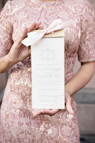 wedding-guest-in-jacquard-dress-holding-ceremony-program-monogram-light-print-pink-ribbon-gold-top