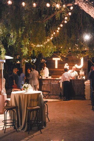 rustic-wedding-reception-cocktail-tables-wood-bar-initial-lights-globe-lighting-jenna-tim-lopez