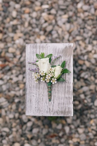 rose-and-purple-boutonniere-on-wood-plank