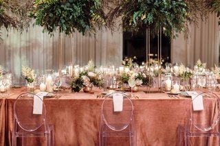 head-table-at-wedding-with-ghost-chairs-and-tall-arrangements-of-greenery