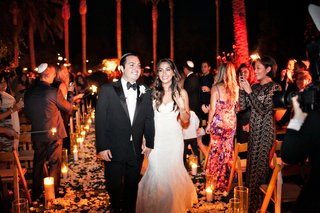 bride-and-groom-leaving-ceremony-evening-ceremony-candlelit-decor-on-aisle
