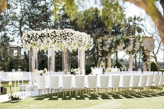 guests-seated-in-white-chairs-gold-legs-around-chuppah-birch-branch-white-flowers-greenery-candles