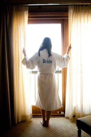 bride-stands-at-window-in-hotel-room-with-white-robe