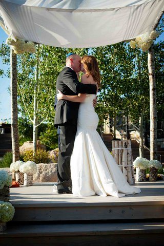 bride-and-groom-kiss-under-tallit-and-birch-ceremony-structure