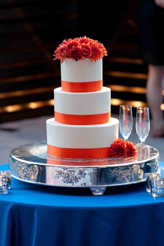 wedding-cake-on-silver-stand-on-blue-table-with-orange-ribbons