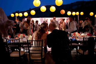 bride-and-groom-kiss-at-night-reception-with-yellow-lanterns