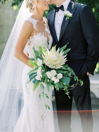 bride-holding-large-bouquet-with-ivory-king-protea-flower-tropical-greenery-illusion-wedding-dress