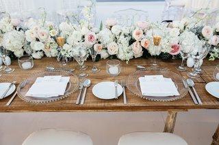 beach-wedding-reception-with-a-wood-head-table-runner-of-pink-peach-white-garden-roses-greenery