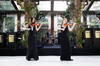 tent-wedding-reception-nature-inspired-decorations-women-in-black-gowns-with-violins-on-dance-floor
