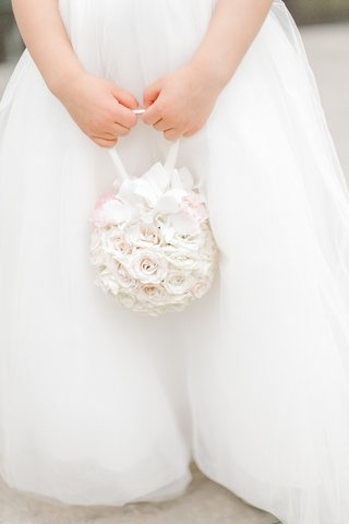 flower-girl-in-a-white-dress-holds-pomander-bouquet-of-white-roses-orchids-a-few-pink-flowers