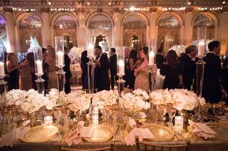 wedding-reception-guests-hanging-out-at-reception-long-table-ivory-centerpiece-tall-candles-plaza