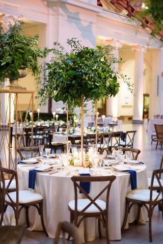 wedding-reception-the-field-museum-greenery-on-gold-stand-wood-vineyard-chair-blue-napkins-round