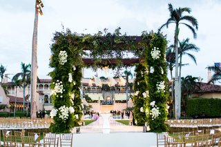 outdoor-wedding-ceremony-structure-wood-arbor-greenery-white-rose-flowers-in-the-round-seating