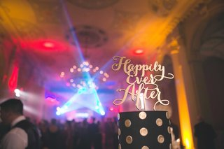 black-and-gold-polka-dot-wedding-cake-with-happily-ever-after-modern-calligraphy-cake-topper-lights