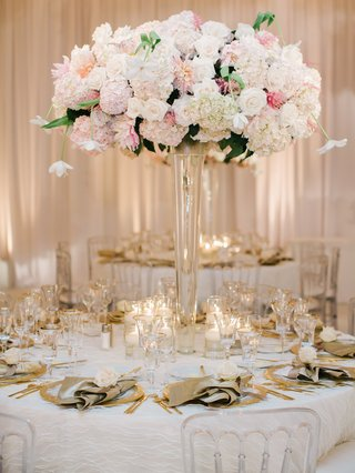 wedding-reception-table-with-centerpiece-of-white-and-pink-flowers-golden-flatware-napkins