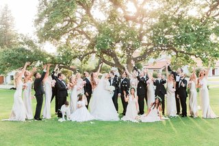 large-bridal-party-in-formal-attire-throwing-confetti-in-the-air-as-bride-and-groom-kiss