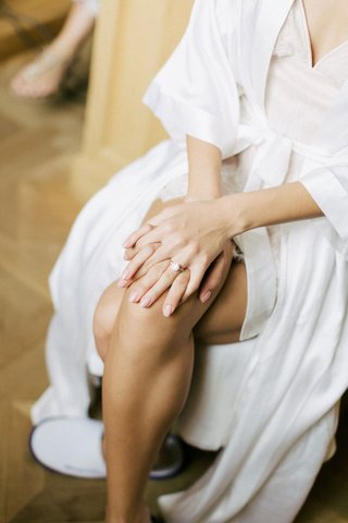 bride-in-white-robe-pale-pink-manicure-for-wedding-day-solitaire-engagement-ring