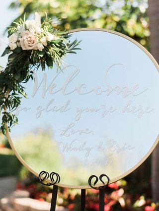 wedding-ceremony-round-mirror-welcome-sign-were-so-glad-youre-here-flowers-and-greenery-on-top