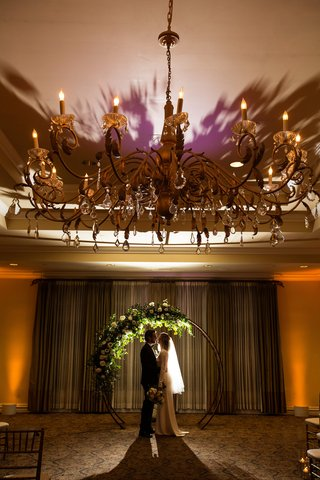 slightly-silhouetted-picture-of-bride-and-groom-posing-by-their-circular-wedding-altar