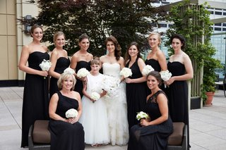 bride-and-bridesmaids-in-black-dresses-with-white-orchid-bouquets-flower-girl-in-white-dress
