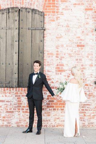 bride-approaching-groom-near-brick-wall