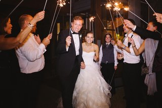 bride-and-groom-walk-through-tunnel-of-friends-with-fireworks