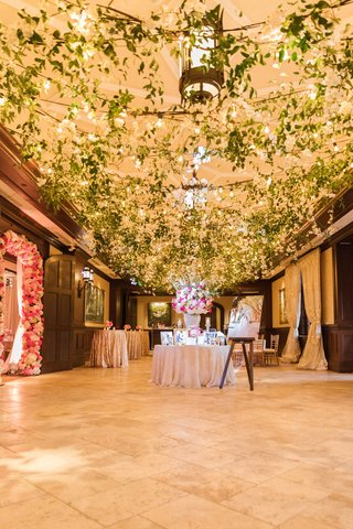 entrance-to-wedding-reception-with-ceiling-covered-with-greenery-and-bistro-lights