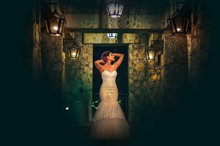 a-bride-in-a-trumpet-white-wedding-dress-poses-in-dark-hallway-with-a-bright-red-flower-in-her-hair