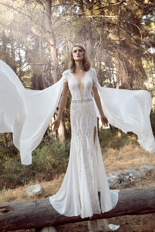 a-sheath-gown-with-intricate-designs-a-thin-belt-a-skirt-slit-a-plunging-neckline-and-capped-sle