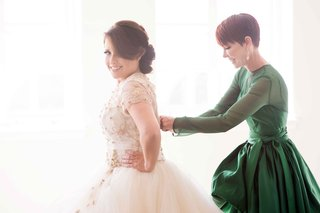 mother-of-bride-helping-daughter-put-on-wedding-dress-in-designer-green-dress-with-long-sleeves