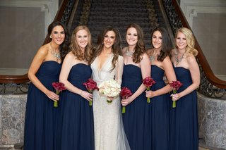 bridesmaids-in-strapless-navy-blue-dresses-with-calla-lily-bouquets-bride-inbal-dror-wedding-dress