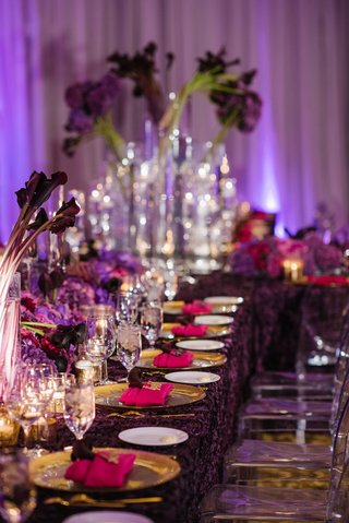 wedding-reception-long-table-with-purple-texture-tablecloth-gold-charger-purple-flowers-pink-napkins