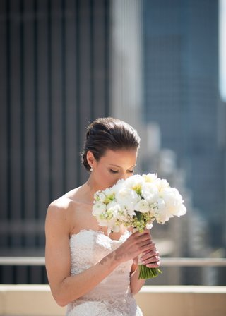 a-bride-smelling-her-bouquet-made-of-white-blooms-on-a-rooftop-in-new-york-city