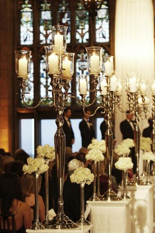 silver-candle-holders-on-white-pedestals