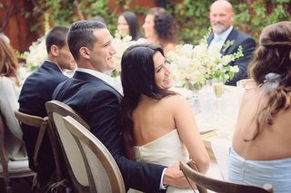 bride-and-groom-smile-at-reception-table