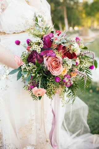 bridal-bouquet-of-greenery-peach-and-red-roses-light-orange-ranunculus-crimson-peony-butterfly