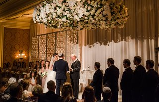 bride-and-groom-with-rabbi-wedding-ceremony-hanging-flower-chuppah-chandelier-lighting-romantic