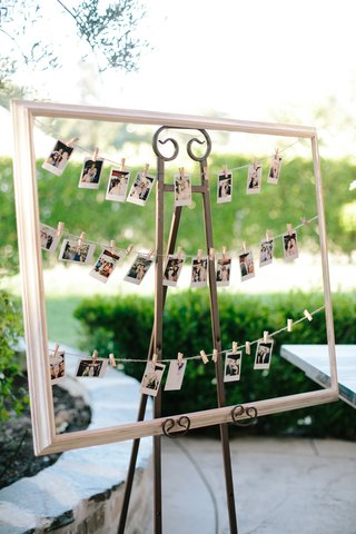 polaroid-photos-for-guest-book-hung-up-in-frame-by-miniature-clothespins
