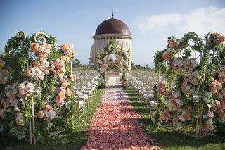 peach-roses-wind-around-a-wrought-iron-gate-at-front-of-aisle