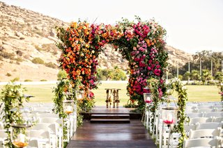 outdoor-wedding-reception-dark-wood-aisle-with-white-chairs-greenery-pink-orange-yellow-flowers