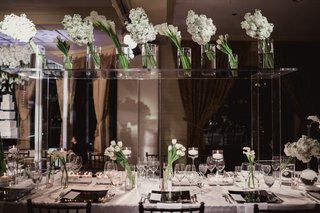 lucite-table-on-top-of-wedding-head-table-to-display-white-flowers