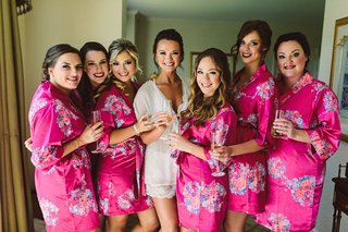 flower-print-robes-bright-pink-flower-design-champagne-glasses-bride-in-white-robe-getting-ready