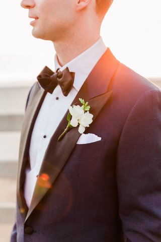 wedding-portraits-groom-photo-close-up-of-boutonniere-white-flowers-greenery-tuxedo-bow-tie