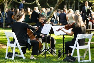 wedding-ceremony-musicians-violin-cello-viola-in-white-chairs-on-lawn-greenery