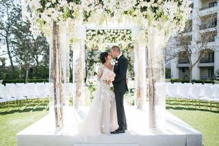 tree-branch-chuppah-with-lucite-structure-white-flowers-greenery-orchids-roses-kiss-couple