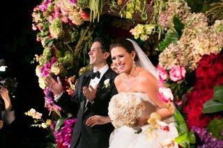 bride-in-vera-wang-wedding-dress-holding-round-ivory-bouquet-under-flower-embellished-chuppah