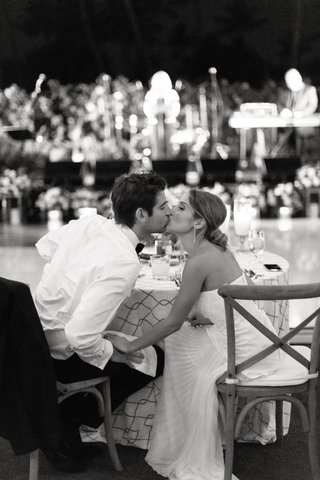 black-and-white-photo-of-bride-and-groom-kissing-at-their-sweetheart-table