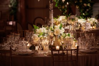 ivory-flowers-at-base-of-birch-branch-holding-up-centerpiece