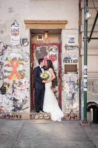 wedding-in-new-york-city-bride-and-groom-kiss-in-doorway-with-graffiti-and-street-art-city-portrait